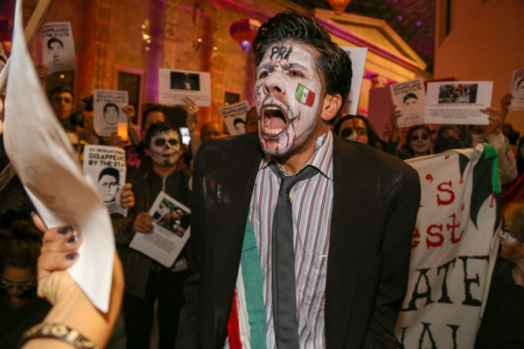 One of the performers plays the Mexican President, attempting to drown out the living shrine. (Photo: Diana More)