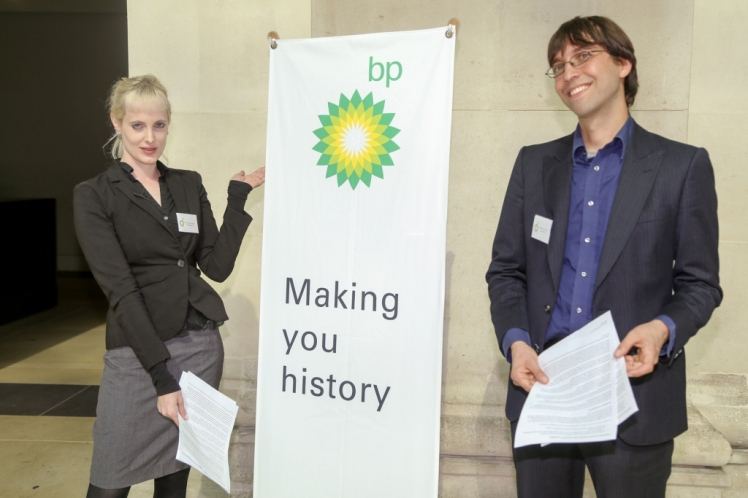 Fake BP staff pose by banner. Photo by Diana More